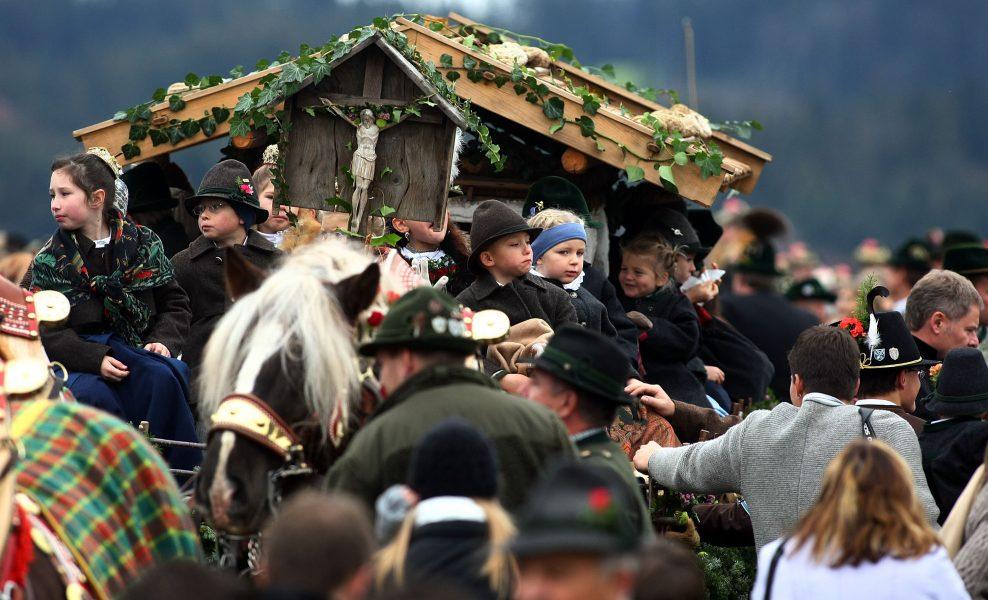 Menschen in Tracht während einer Prozession mit Pferden